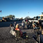 RV site with people sitting in a circle talking